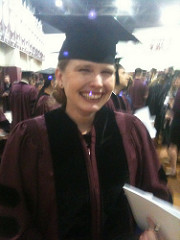 Adrienne smiling in line waiting to graduate with a PhD