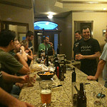A group of people gathered around a counter drinking homebrew and eating