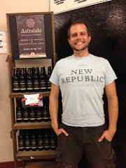 Dean smiling in front of a store display of Astrolabe beer by New Republic Brewing