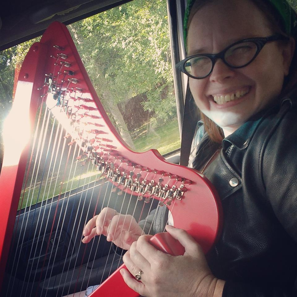 Adrienne playing a red lap harp