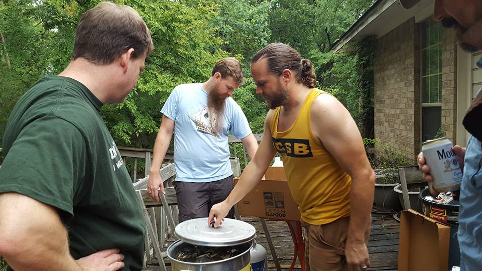 Dean with three other people on the back porch using old brewing equipment to cook crabs