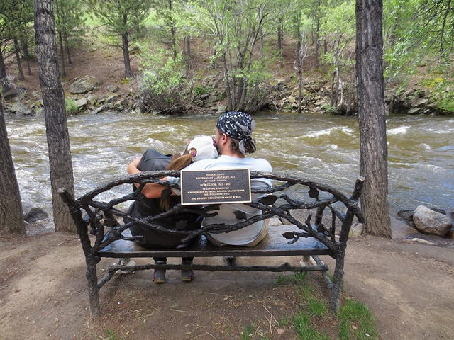Dean and Adrienne snuggling on a bench in front of a river