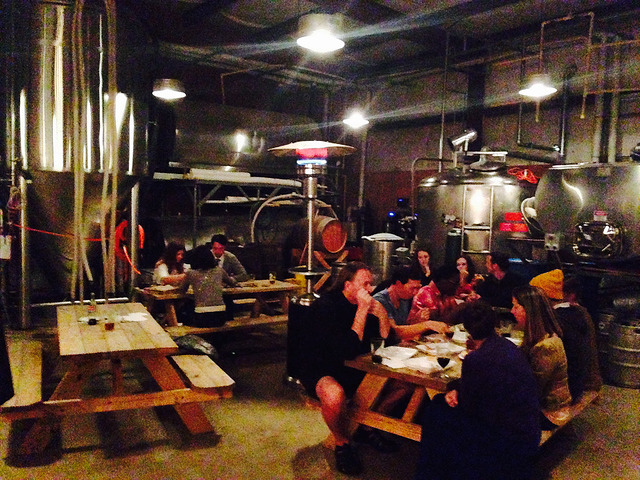 A group of tables with people eating thanksgiving dinner among brewery equipment.
