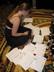 Adrienne sitting on the floor surrounded by beer judging sheets, trying to make a choice