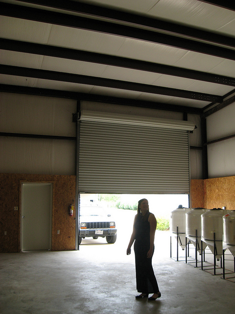 Adrienne standing in a small warehouse with five plastic fermenters and nothing else