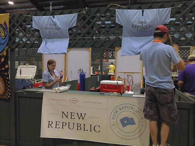 A booth at a festival. Adrienne is inside selling beer