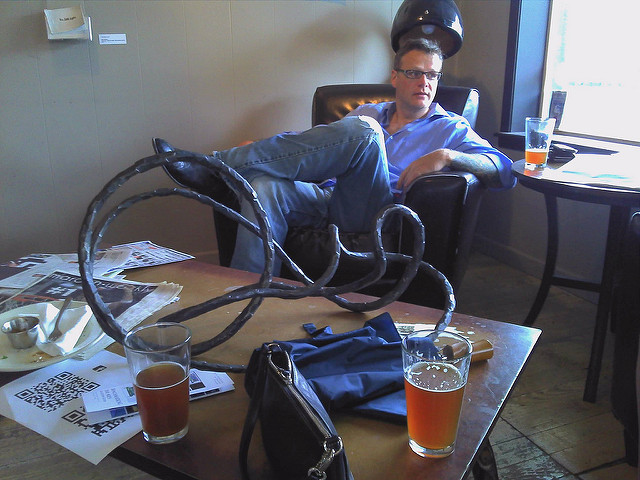 A man reclining in a chair at a cafe after buying a pint of beer