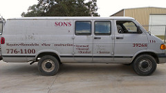 An old, gray delivery van that needs help